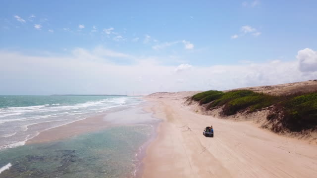aerial drone view of a 4x4 jeep car vehicle driving on the beach surf trip. - 四輪駆動車点の映像素材/bロール