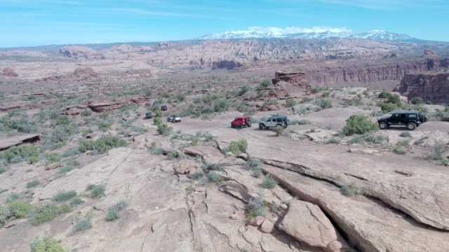 Aerial drone view of a 4x4 vehicles driving off-road on a dirt road in Moab, Utah.