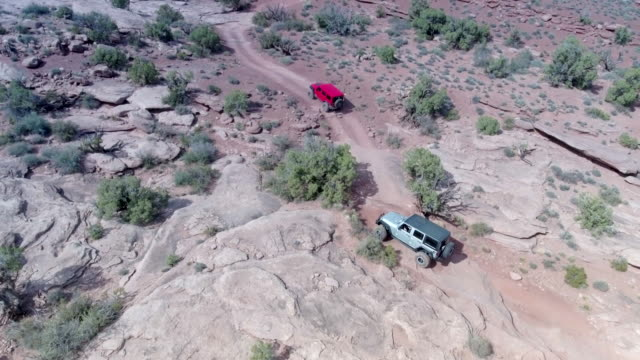 stockvideo's en b-roll-footage met aerial drone view of a 4x4 vehicles driving off-road on a dirt road in moab, utah. - moab utah