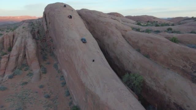 aerial drone view of a 4x4 vehicles driving off-road on a dirt road in moab, utah. - ジープ点の映像素材/bロール