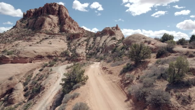 aerial drone view of a 4x4 vehicles driving off-road on a dirt road in moab, utah. - strada in terra battuta video stock e b–roll