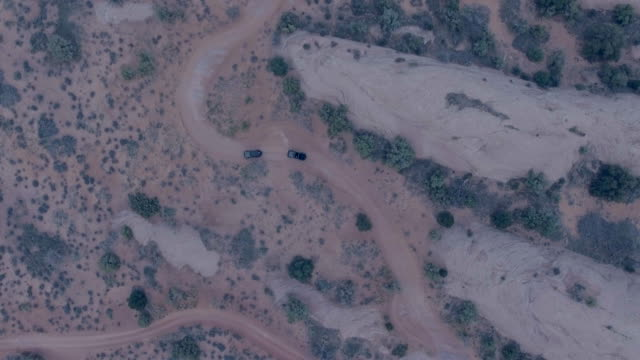 aerial drone view of a 4x4 vehicles driving off-road on a dirt road in moab, utah. - goodsportvideo stock videos and b-roll footage