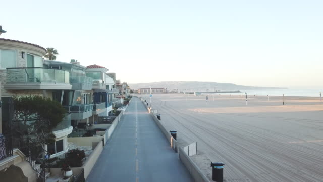 vídeos y material grabado en eventos de stock de aerial drone view of a beach boardwalk strand at sunrise in california, ocean and empty beach. - bulevar