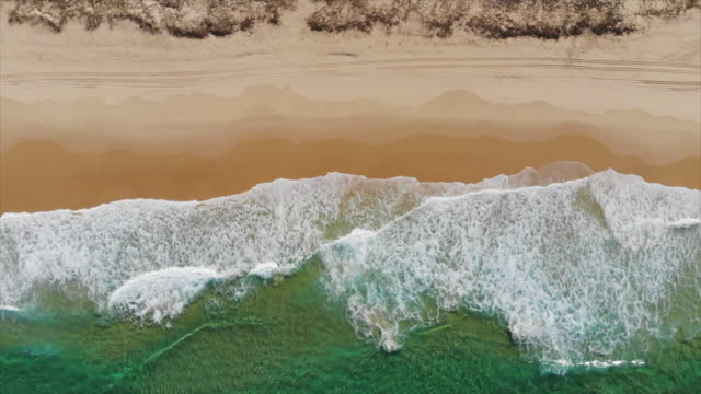 aerial drone view of a beach sandbar, surf and waves breaking. - slow motion - beach stock videos & royalty-free footage