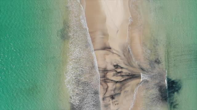 vídeos de stock e filmes b-roll de aerial drone view of a beach sandbar, surf and waves breaking. - slow motion - banco de areia