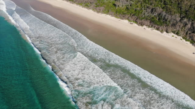 aerial drone view of a beach sandbar, surf and waves breaking. - slow motion - ニューサウスウェールズ州点の映像素材/bロール