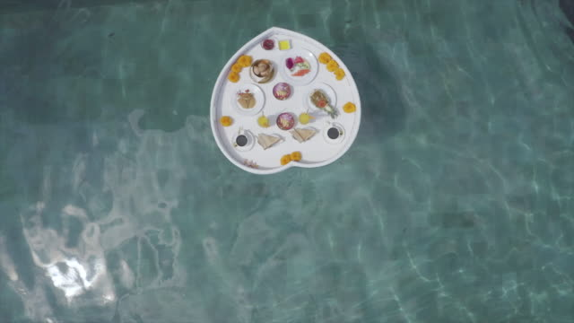 aerial drone view of a breakfast food tray floating on a heart shaped tray in a pool at a villa resort hotel  traveling. - リゾート点の映像素材/bロール