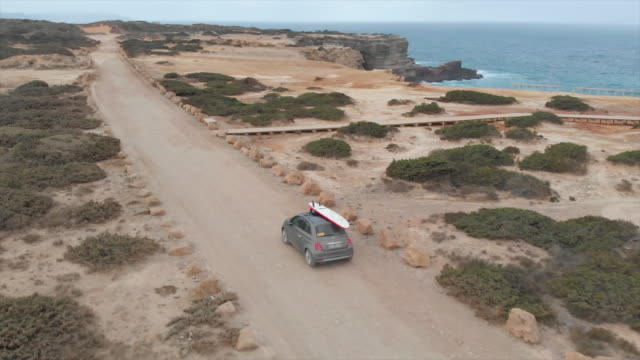 stockvideo's en b-roll-footage met aerial drone view of a car driving on a dirt road with a surfboard on top. - surfbord