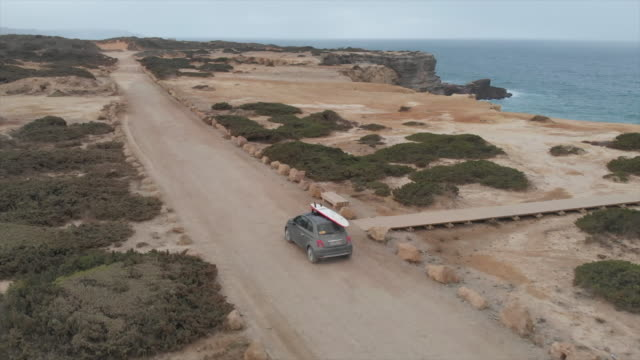 vídeos y material grabado en eventos de stock de aerial drone view of a car driving on a dirt road with a surfboard on top. - time-lapse - tabla de surf