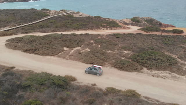 Aerial drone view of a car driving on a dirt road with a surfboard on top. - Slow Motion