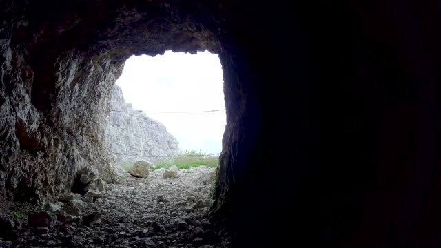 vídeos de stock, filmes e b-roll de aerial drone view of a cave and hiking in the mountains. - goodsportvideo