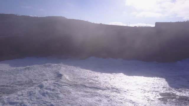 Aerial drone view of a cliff and surfers surfing waves on his surfboard.