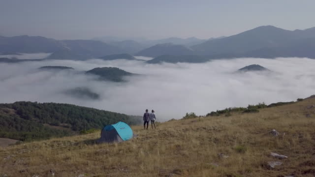 Aerial drone view of a couple looking at the foggy landscape