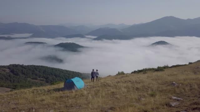 vídeos y material grabado en eventos de stock de aerial drone view of a couple looking at the foggy landscape - tienda de campaña