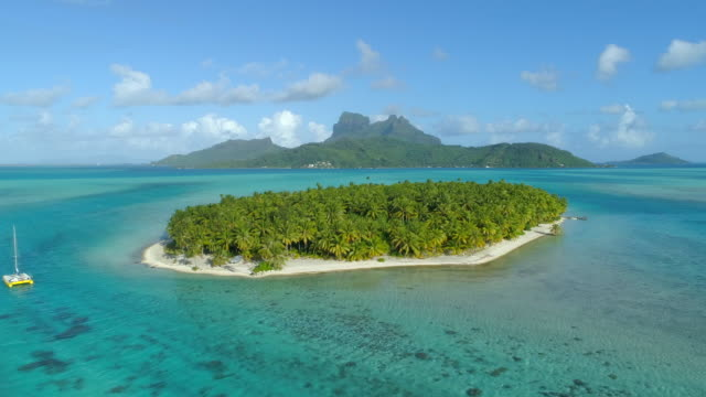 Aerial drone view of a deserted island near Bora Bora tropical island.