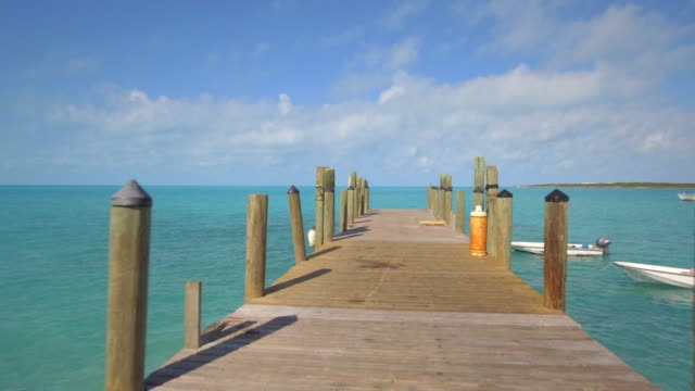 Aerial drone view of a dock pier on a tropical island beach and coast in the Bahamas, Caribbean.