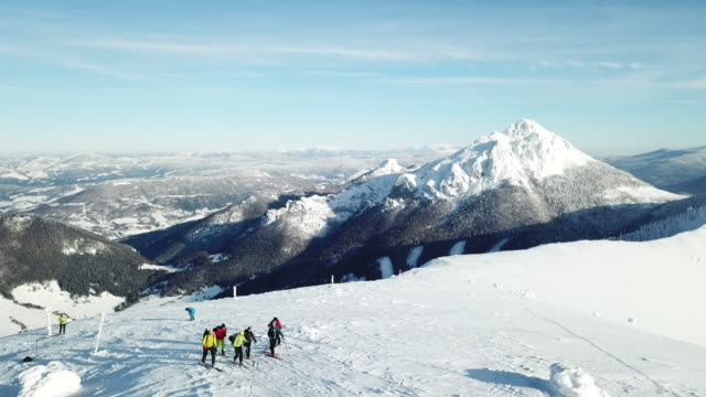 aerial drone view of a group of eight skiers cross country skiing uphill on a snow covered mountain in fresh powder snow. - slow motion - längd bildbanksvideor och videomaterial från bakom kulisserna