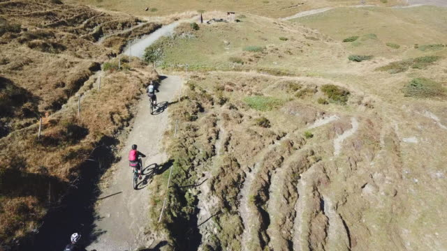 vídeos de stock, filmes e b-roll de aerial drone view of a group of mountain bikers on a singletrack trail. - trilho para bicicleta esporte ao ar livre