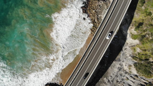 aerial drone view of a highway near the ocean and cars vehicles driving on a road through a forest with surfboards on top. - slow motion - driving stock videos & royalty-free footage
