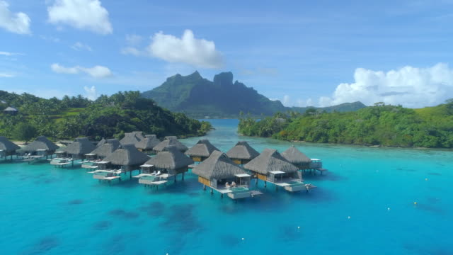 aerial drone view of a luxury resort and overwater bungalows in bora bora tropical island. - bora bora aerial stock videos and b-roll footage