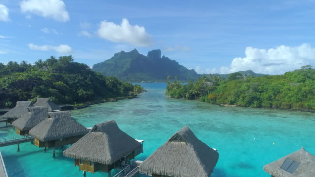 aerial drone view of a luxury resort and overwater bungalows in bora bora tropical island. - フランス領ポリネシア点の映像素材/bロール