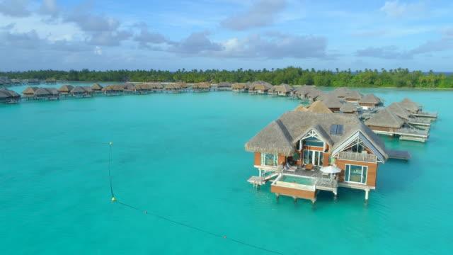 aerial drone view of a luxury resort and overwater bungalows in bora bora tropical island. - french polynesia stock videos & royalty-free footage