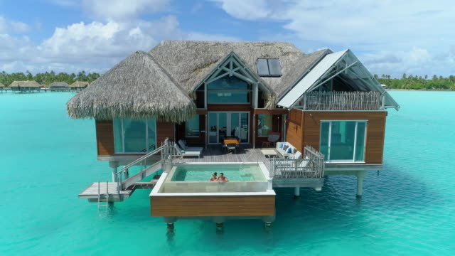 aerial drone view of a luxury resort and overwater bungalows in bora bora tropical island. - luxus stock-videos und b-roll-filmmaterial