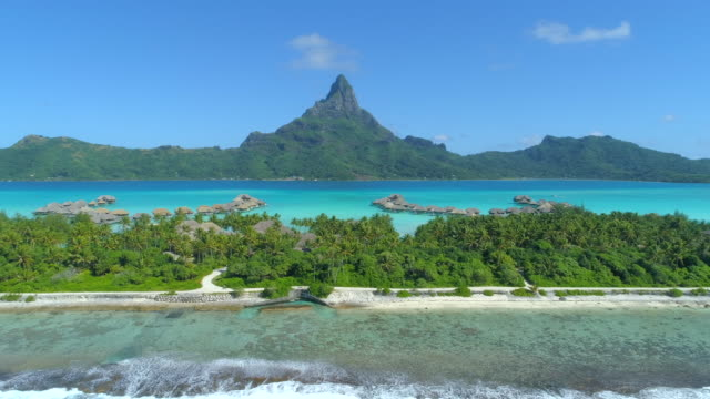 vidéos et rushes de aerial drone view of a luxury resort and overwater bungalows in bora bora tropical island. - bora bora