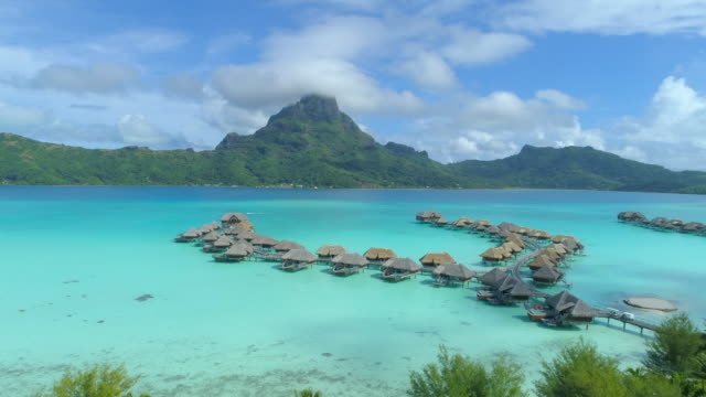 aerial drone view of a luxury resort and overwater bungalows in bora bora tropical island. - time-lapse - bora bora aerial stock videos and b-roll footage
