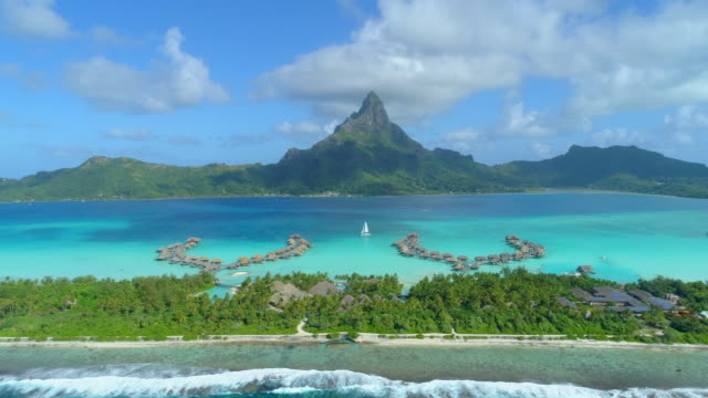 stockvideo's en b-roll-footage met aerial drone view of a luxury resort and overwater bungalows in bora bora tropical island. - time-lapse - frans polynesië