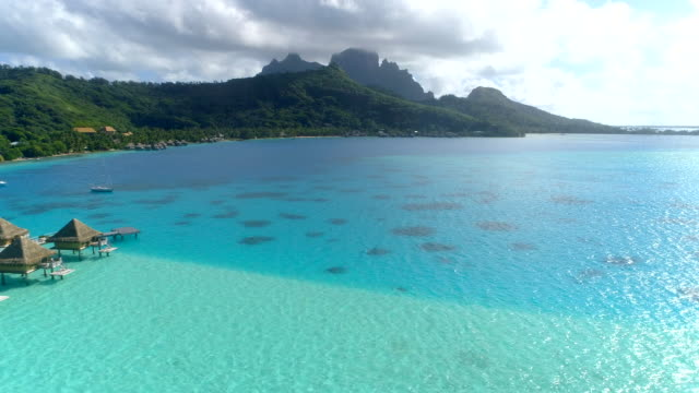 vídeos de stock, filmes e b-roll de aerial drone view of a luxury resort and overwater bungalows in bora bora tropical island. - polinésia