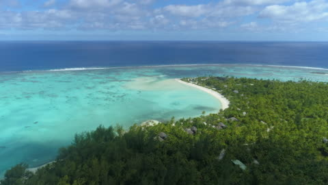 vidéos et rushes de aerial drone view of a luxury resort hotel on a scenic tropical island in french polynesia. - plage
