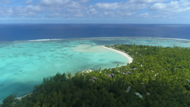 vidéos et rushes de aerial drone view of a luxury resort hotel on a scenic tropical island in french polynesia. - lagon