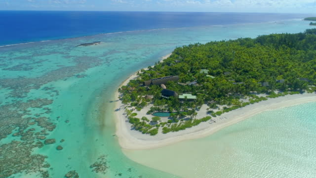 vídeos de stock, filmes e b-roll de aerial drone view of a luxury resort hotel on a scenic tropical island in french polynesia. - polinésia francesa