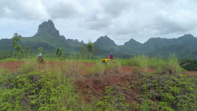 aerial drone view of a man and woman couple driving atv quad runner vehicles up hills. - フランス海外領点の映像素材/bロール