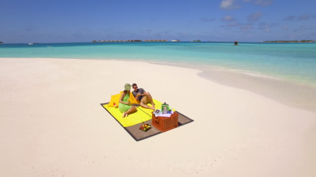 Aerial drone view of a man and woman couple having a picnic meal on a tropical island beach.