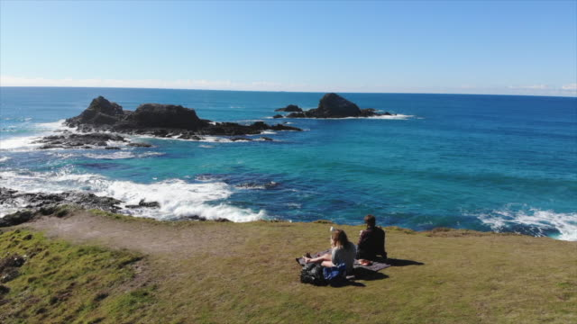 aerial drone view of a man and woman couple having a picnic on a view cliff over the ocean. - slow motion - ニューサウスウェールズ州点の映像素材/bロール