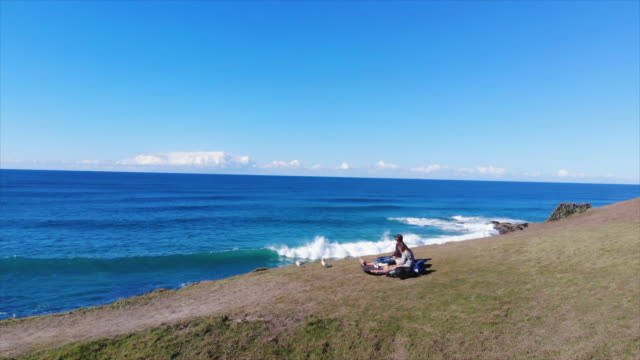 aerial drone view of a man and woman couple having a picnic on a view cliff over the ocean. - slow motion - picnic stock videos & royalty-free footage