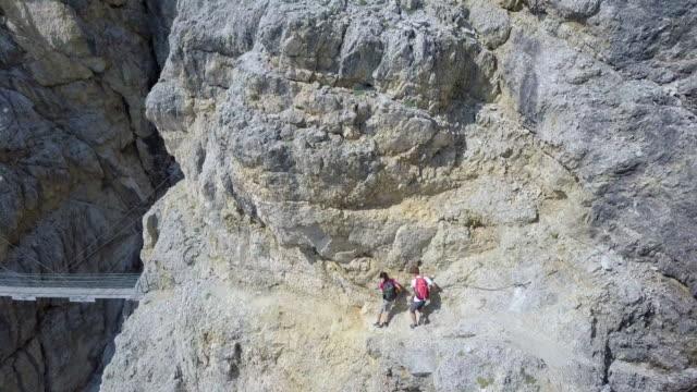 vídeos de stock, filmes e b-roll de aerial drone view of a man and woman couple hiking a bridge in the mountains. - goodsportvideo
