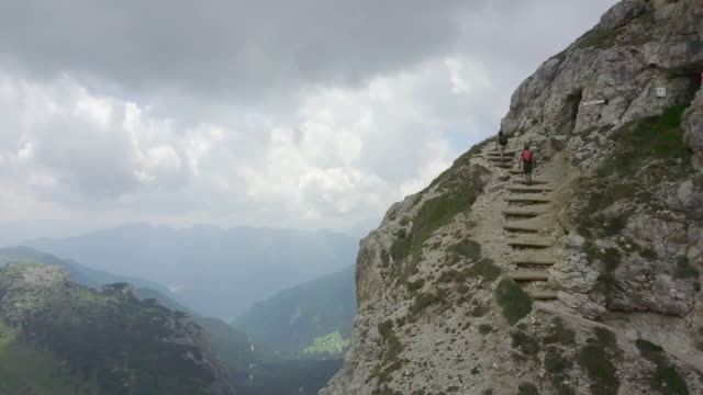 vídeos de stock, filmes e b-roll de aerial drone view of a man and woman couple hiking in the mountains. - goodsportvideo