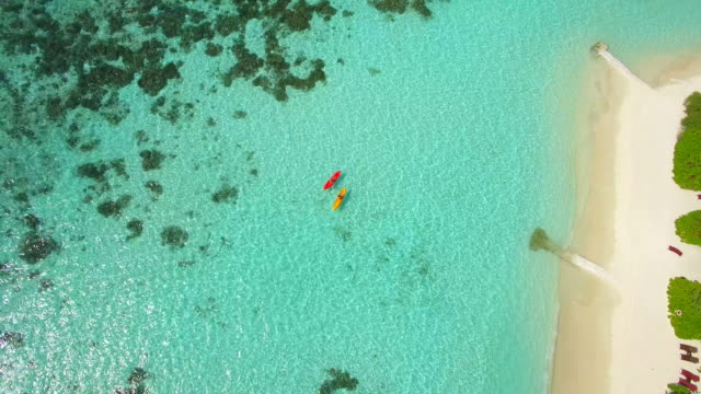 aerial drone view of a man and woman couple kayaking around a tropical island. - kayaking stock videos & royalty-free footage