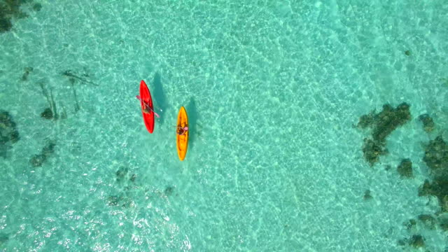 Aerial drone view of a man and woman couple kayaking around a tropical island.