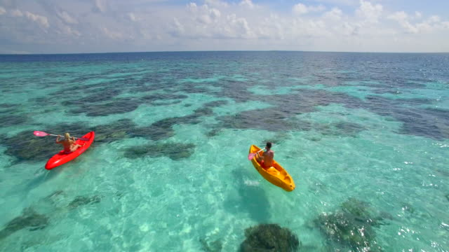 aerial drone view of a man and woman couple kayaking around a tropical island. - kajakdisziplin stock-videos und b-roll-filmmaterial