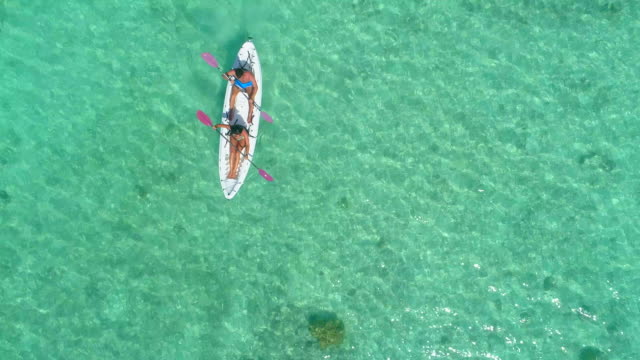 vidéos et rushes de aerial drone view of a man and woman couple kayaking on a tandem kayak in scenic tropical islands. - océan pacifique sud