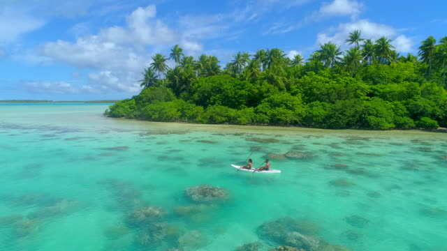 Aerial drone view of a man and woman couple kayaking on a tandem kayak in scenic tropical islands.