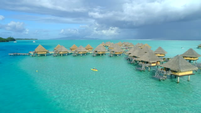 aerial drone view of a man and woman couple on a tandem sea kayak in bora bora tropical island near overwater bungalows. - bora bora aerial stock videos and b-roll footage