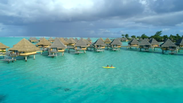 aerial drone view of a man and woman couple on a tandem sea kayak in bora bora tropical island near overwater bungalows. - bora bora stock videos & royalty-free footage