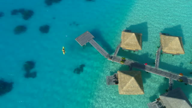Aerial drone view of a man and woman couple on a tandem sea kayak in Bora Bora tropical island near overwater bungalows.