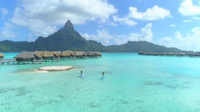 vídeos de stock, filmes e b-roll de aerial drone view of a man and woman couple on sup stand-up paddleboards at a luxury resort with overwater bungalows in bora bora tropical island. - polinésia francesa