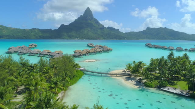 aerial drone view of a man and woman couple on sup stand-up paddleboards at a luxury resort with overwater bungalows in bora bora tropical island. - フランス領ポリネシア点の映像素材/bロール